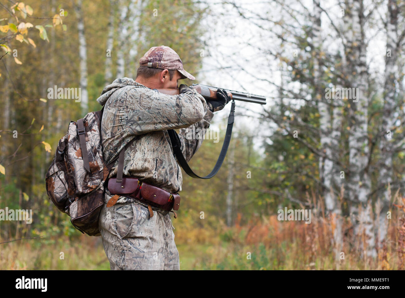 hunter in camouflage taking aim from a hunting gun in the wildfowl - Stock Image