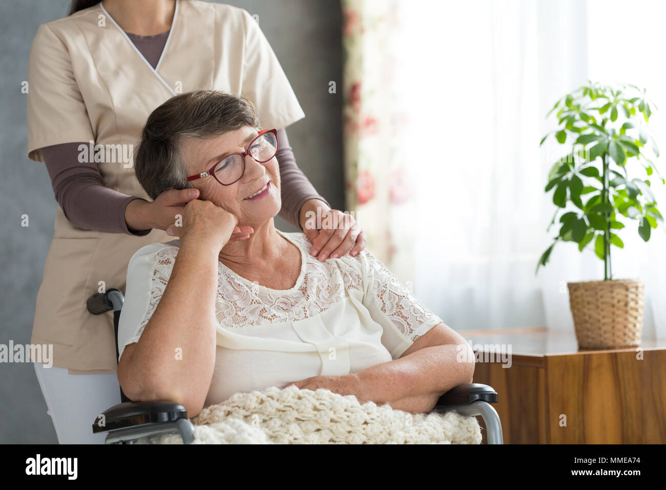 Paralyzed pensioner in wheelchair resting after successful rehabilitation session - Stock Image