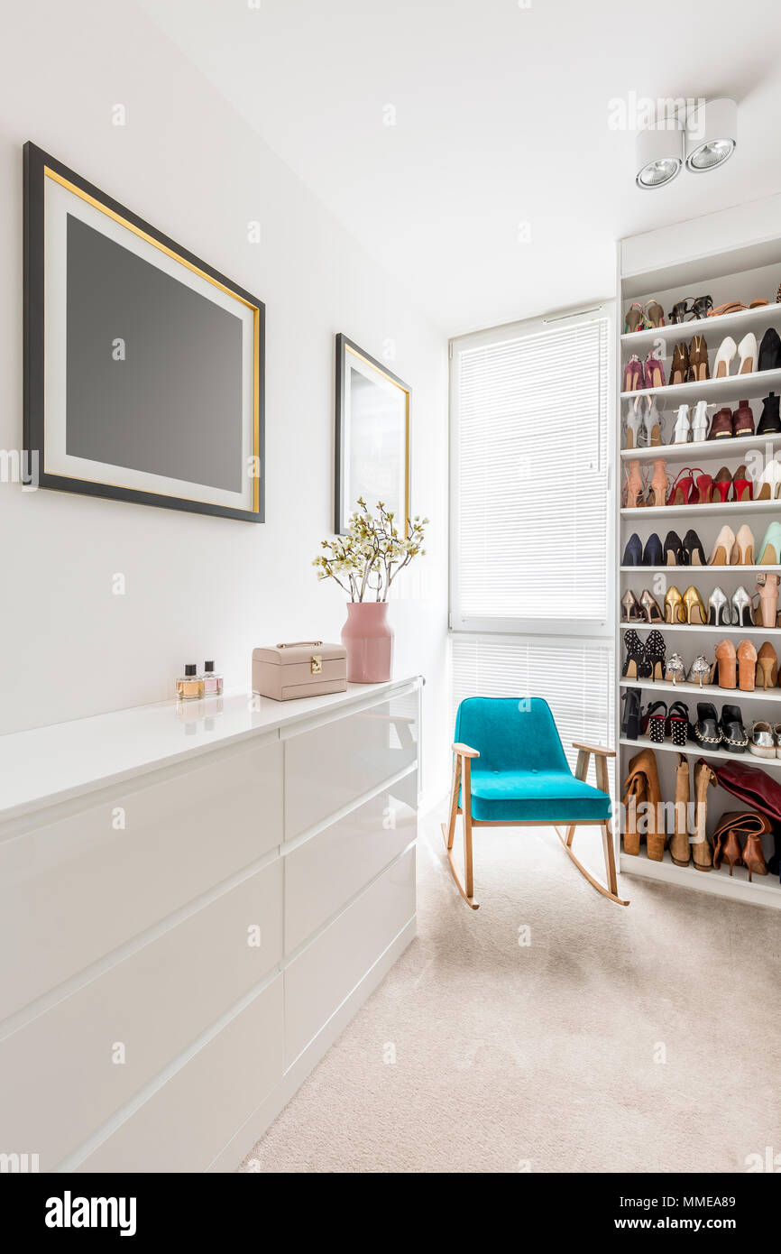 Elegant White Walk In Closet With Shoes Organized On Shelves, Window  Blinds, Sideboard, Blue Armchair And Pink Pastel Details