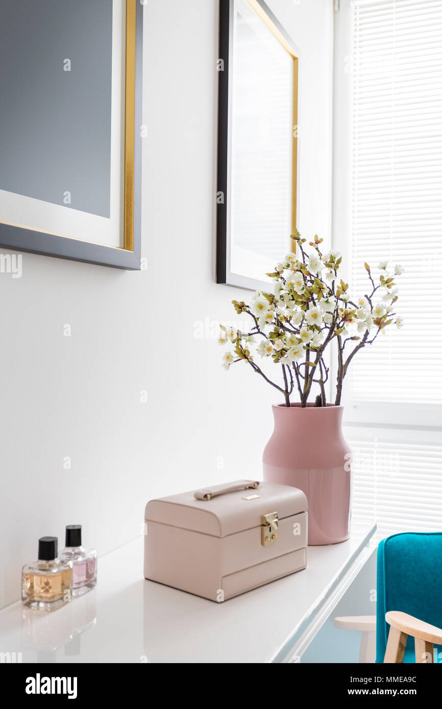 Interior design of white womans room with pink pastel decoration vase flowers blue armchair and painting