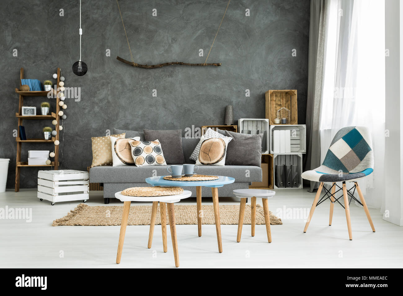 Modern minimalistic and bright living room in shades of cyan with sofa full of cushions, chair, three coffee tables, carpet and stillage made of woode Stock Photo