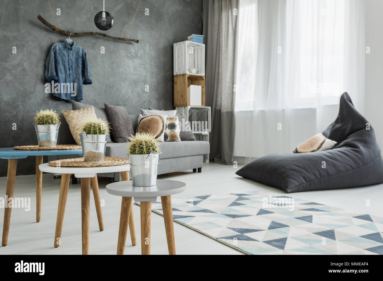 Modern minimalistic and bright living room in shades of cyan with sofa, bean bag chair, three coffee tables with cactuses on, carpet and stillage made - Stock Image