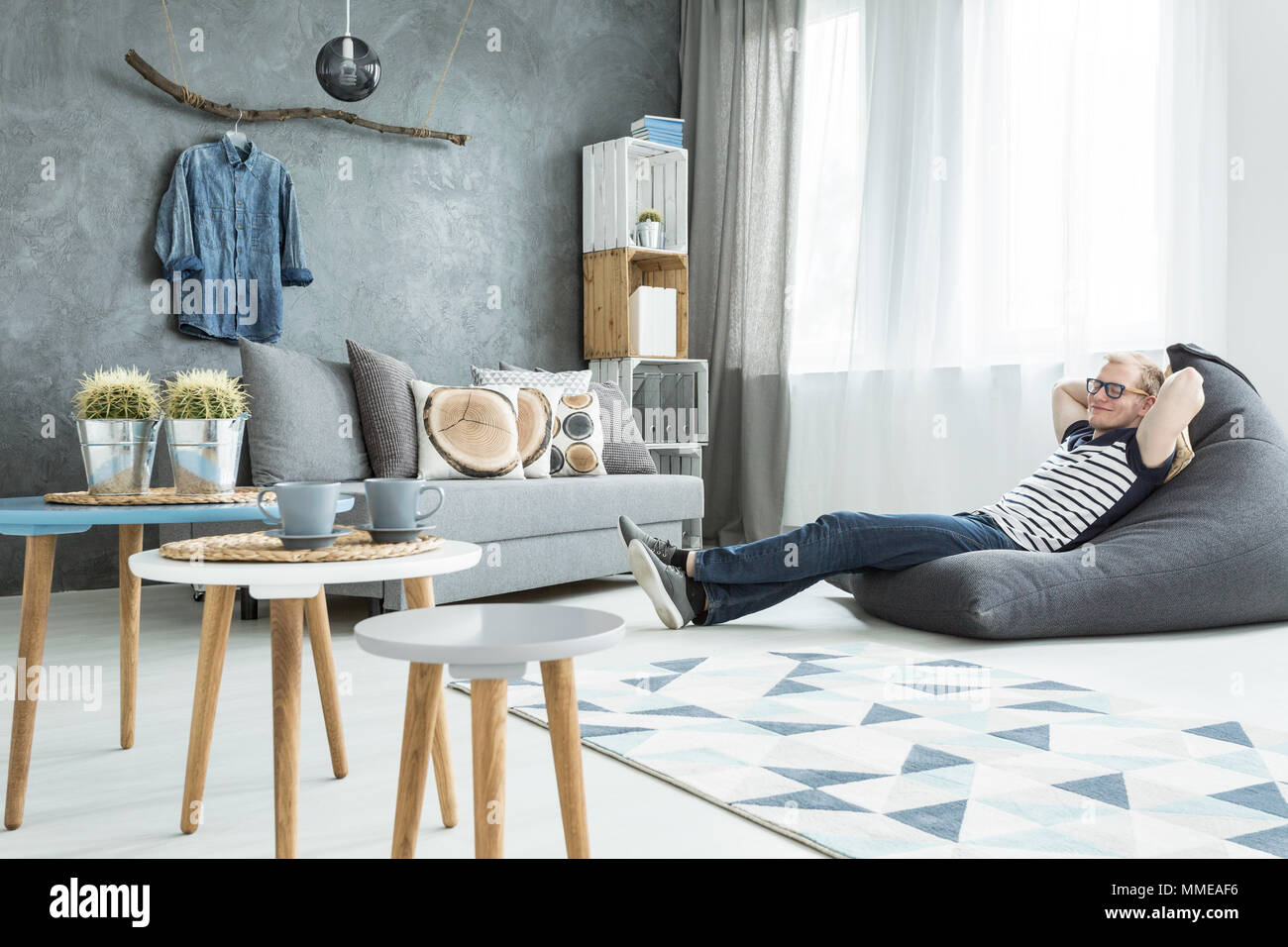 Modern minimalistic and bright living room in shades of cyan with sofa, three coffee tables, carpet, stillage made of wooden cases and a man sitting o - Stock Image