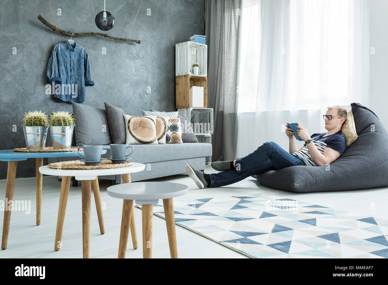 Modern style interior in grey with sofa, stylish futniture, man sitting on a bean bag - Stock Image
