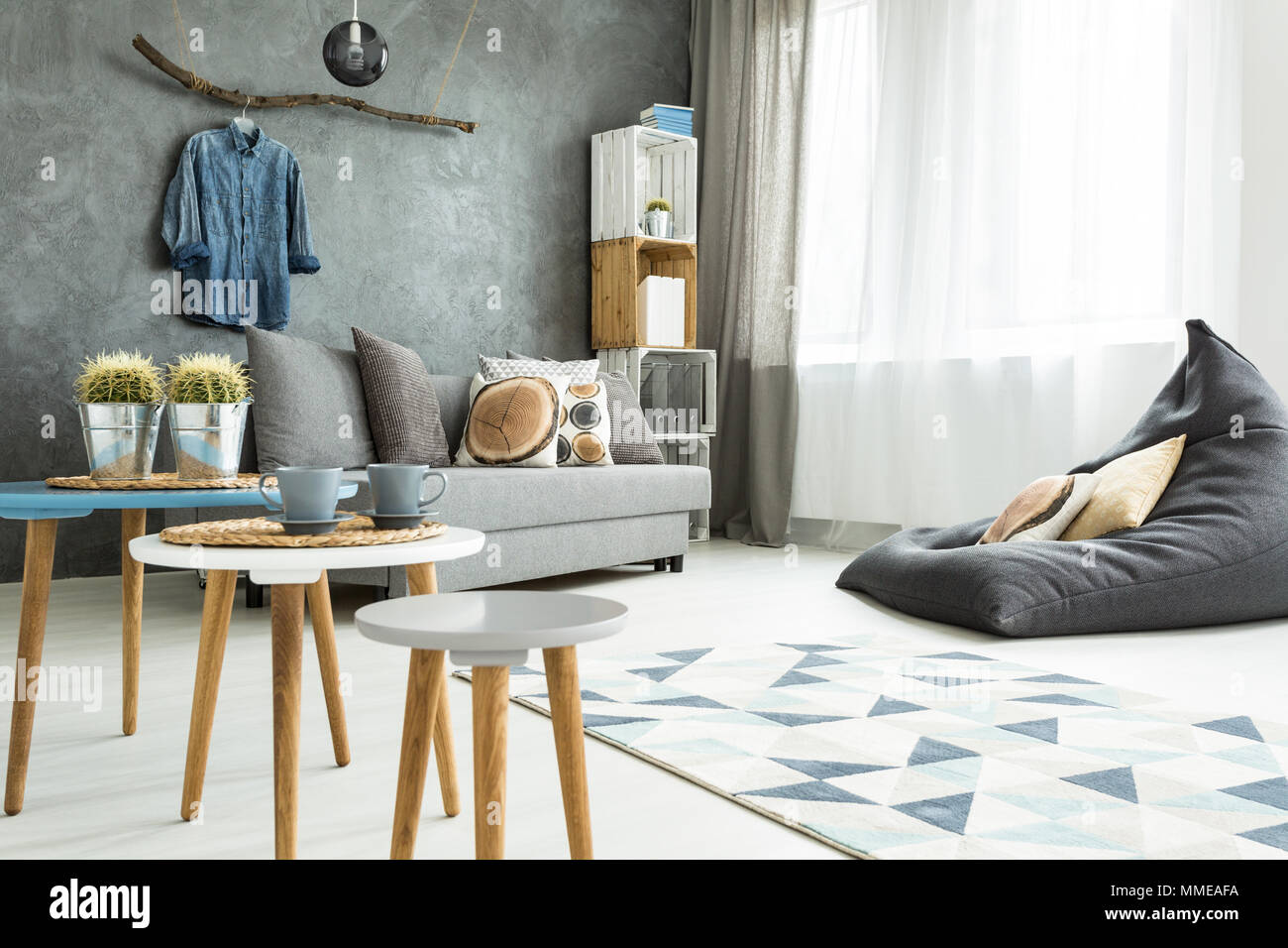 Modern minimalistic and bright living room in shades of cyan with sofa, bean bag chair, three coffee tables, carpet and stillage made of wooden cases - Stock Image
