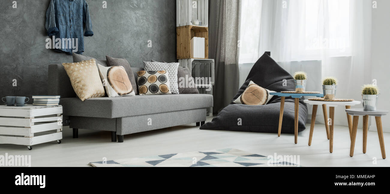 Grey corner of a modern apartment, with a comfy sofa and a sitting sack with pillows imitating wood trunks - Stock Image