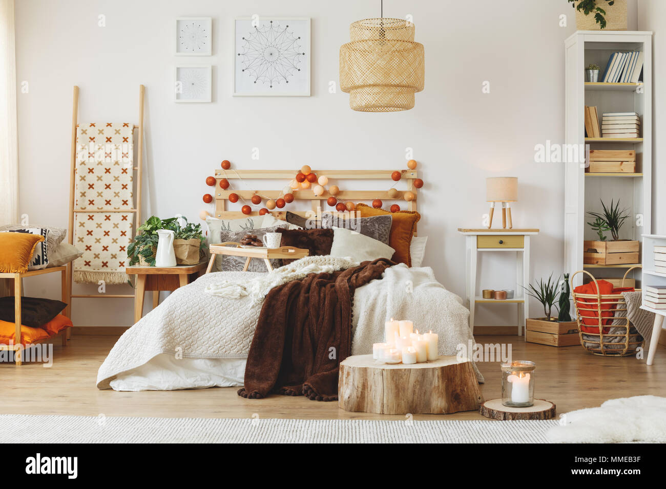 Cozy spacious fully furnished room with big messy bed - Stock Image