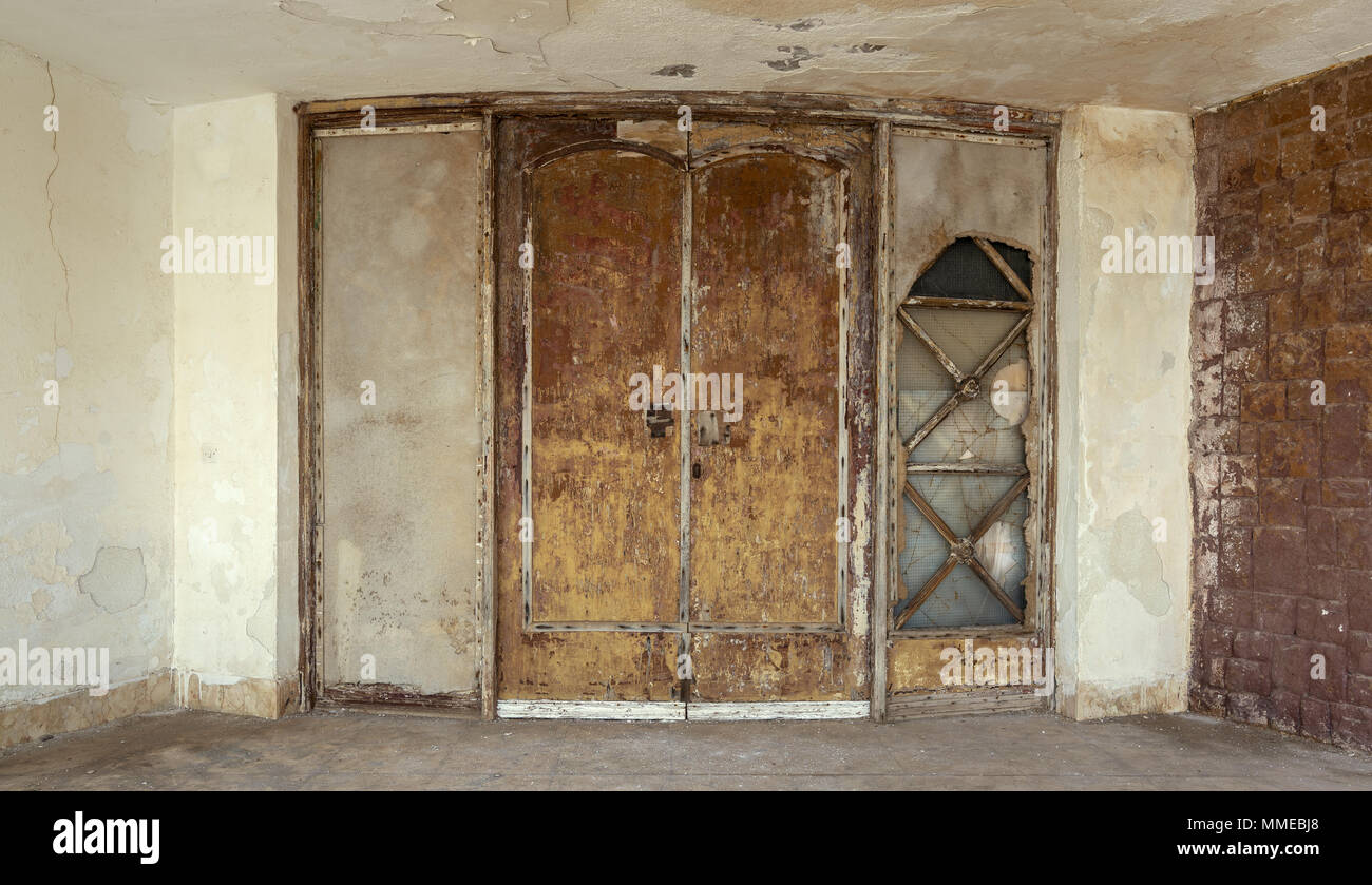 Abandoned old grunge weathered wooden double leaves door and brown stone bricks wall - Stock Image