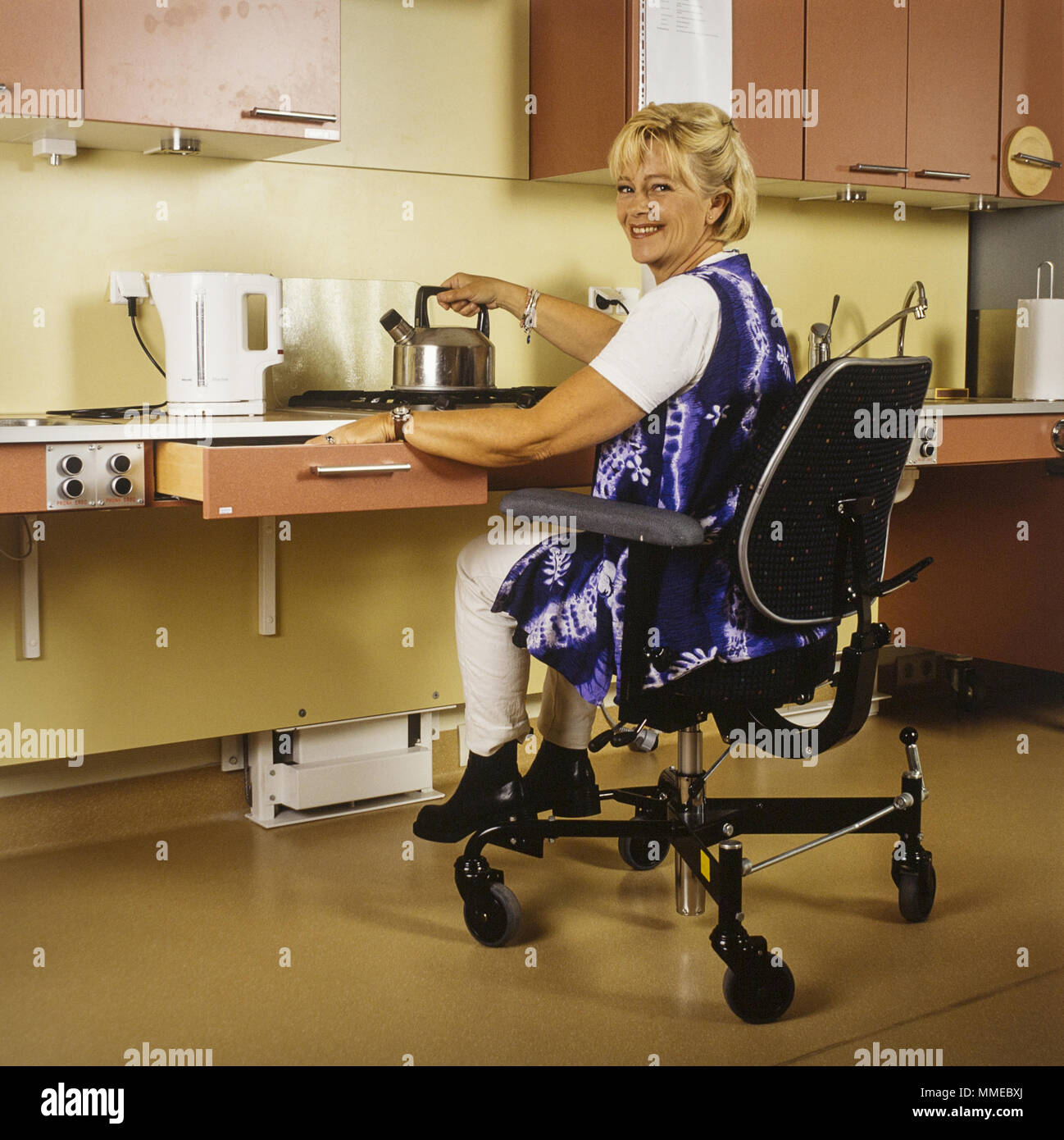 Handicapped woman in handicap kitchen - accessible kitchen for ...