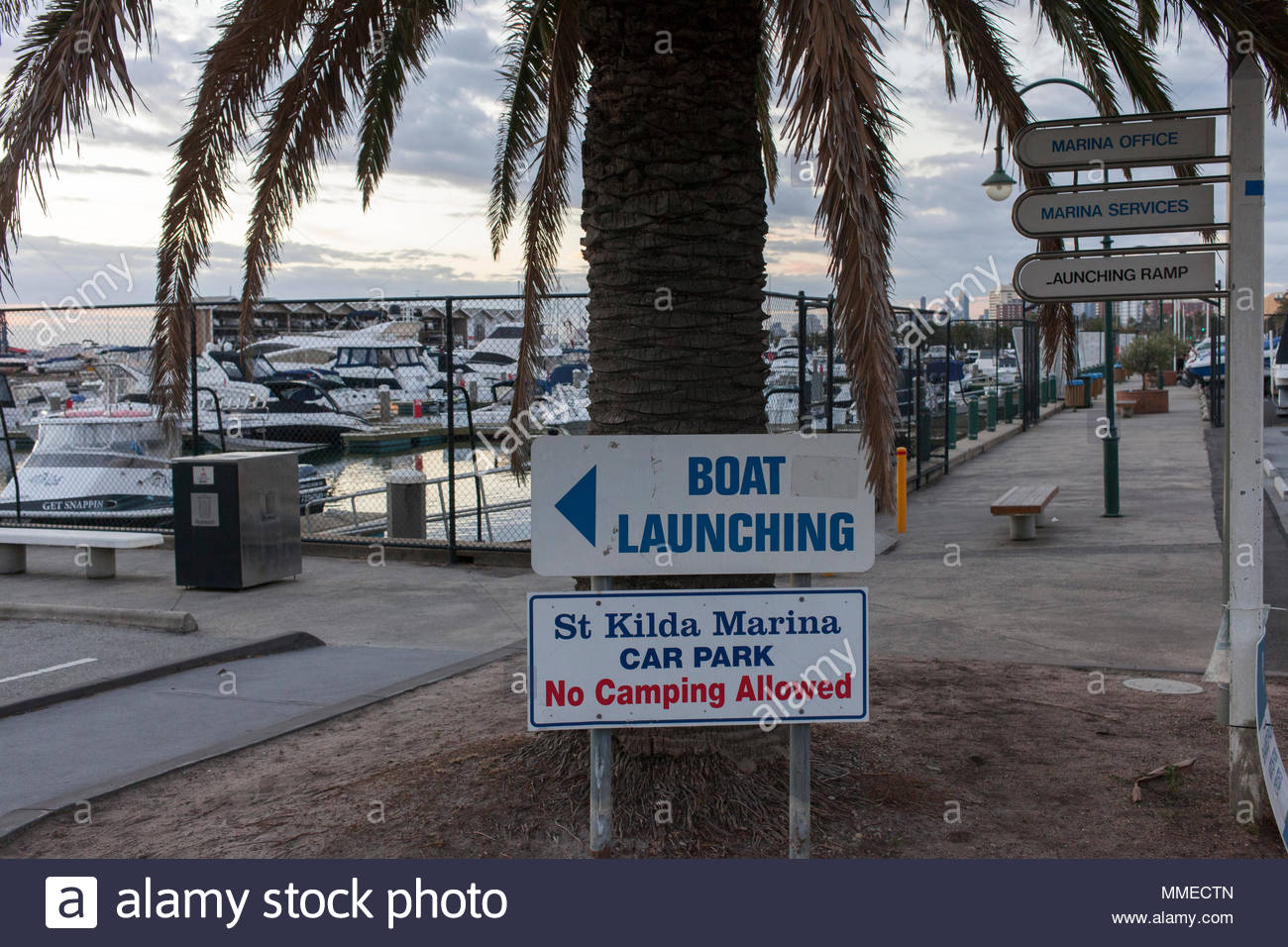 St Kilda Marina Car Park and Boat Launching Sign with No Camping Aloud, under a palm tree with boats in the background - Stock Image