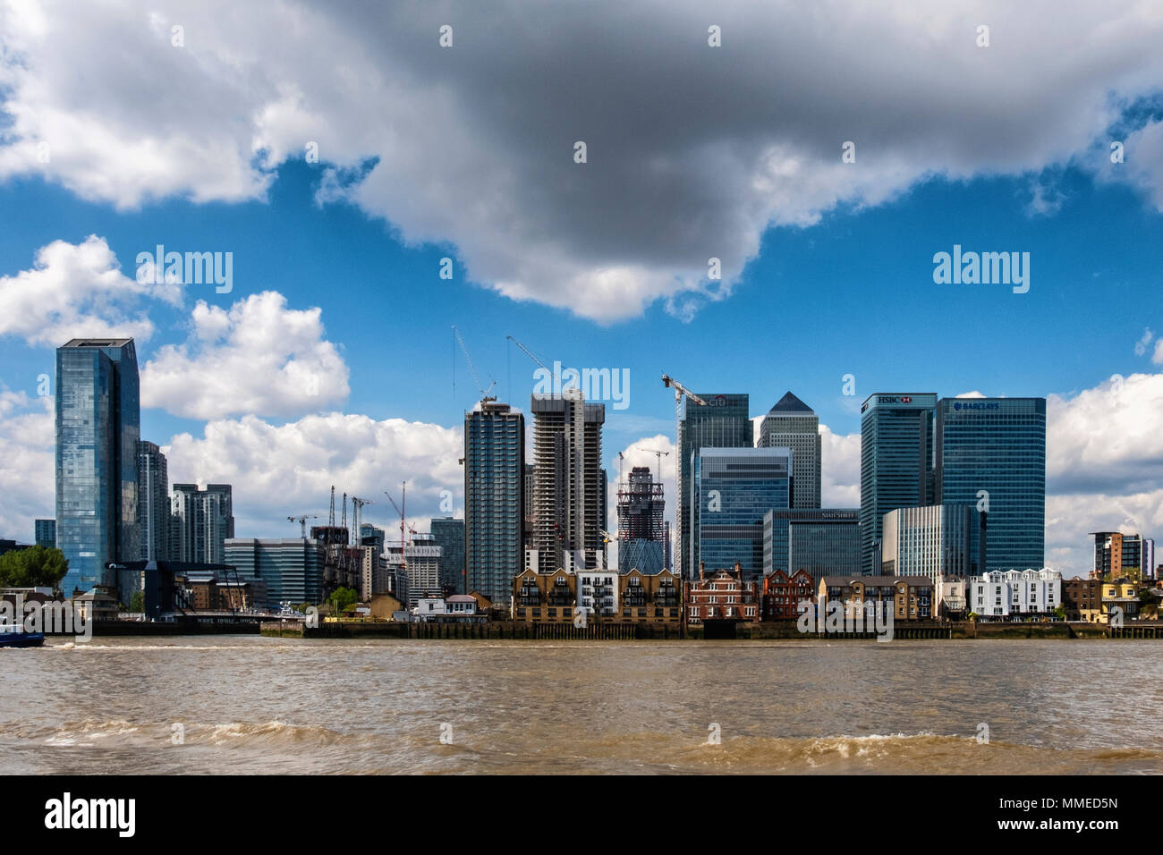 London, Isle of Dogs City skyline view. New-build luxury apartment buildings under construction,Canary Wharf Financial district & traditional old rive - Stock Image