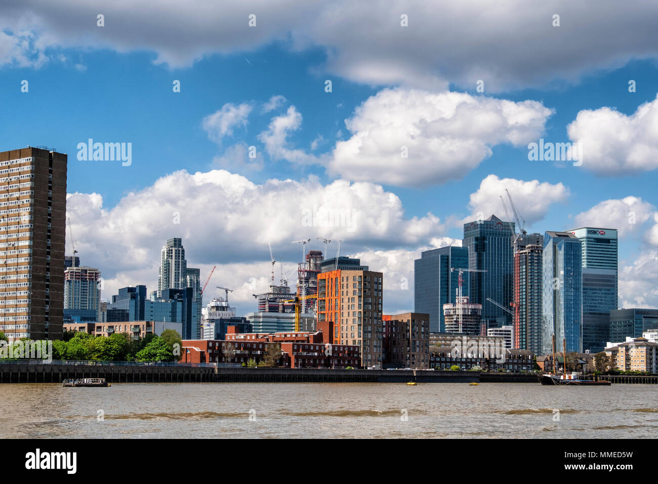 London, Isle of Dogs City skyline view. New-build luxury apartment buildings under construction and Canary Wharf Financial district - Stock Image