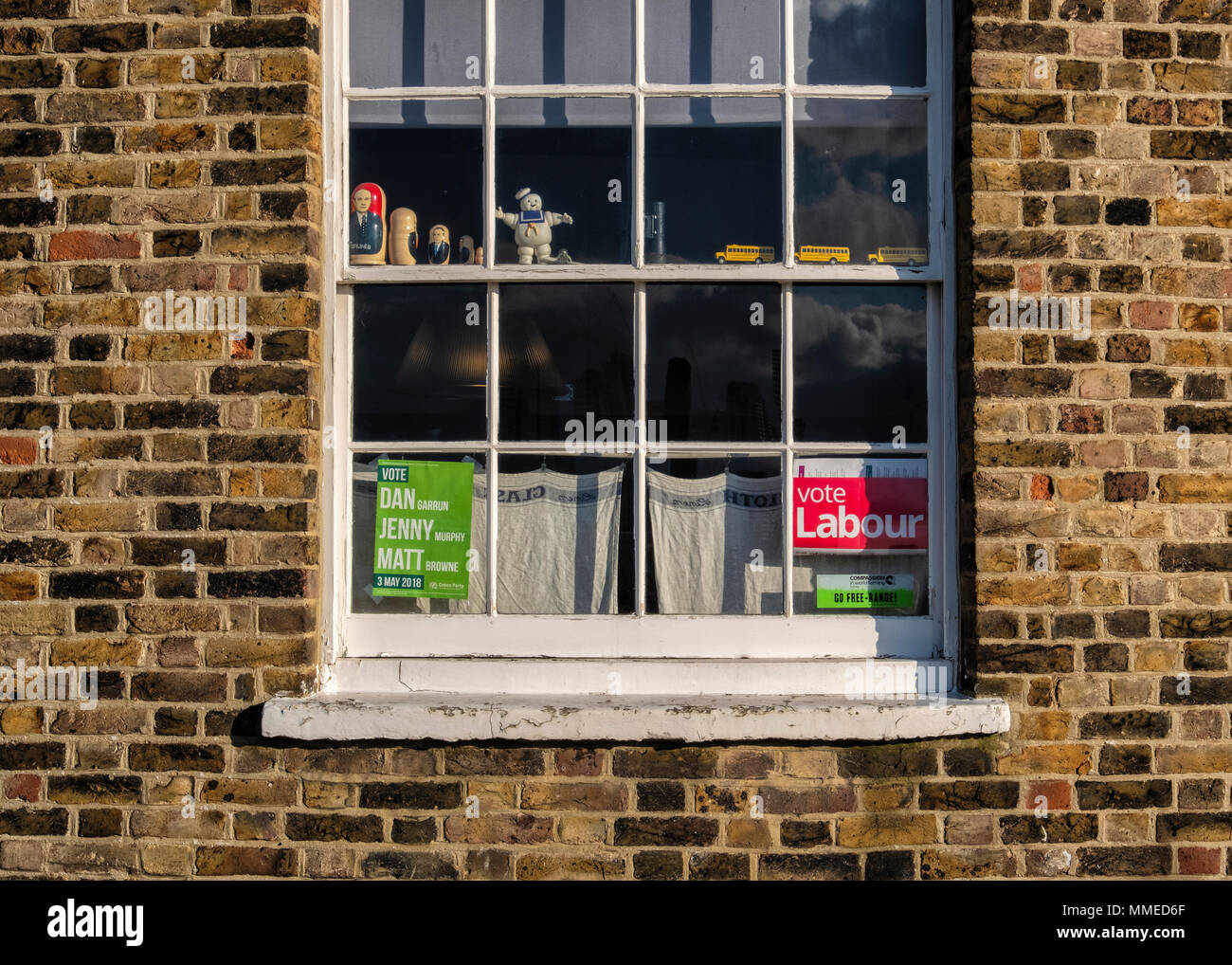 London Greenwich. Election posters for Labour Party & Green Party and ornaments in window of suburban home - Stock Image