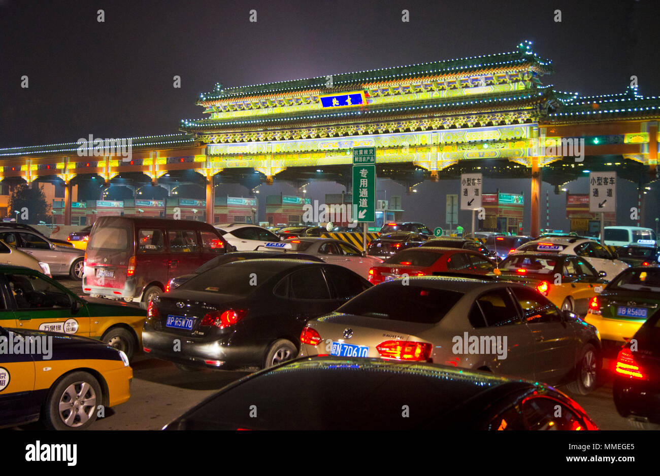 A traffic queue at toll booths on one of the main road in Beijing, China, photographed at night. - Stock Image
