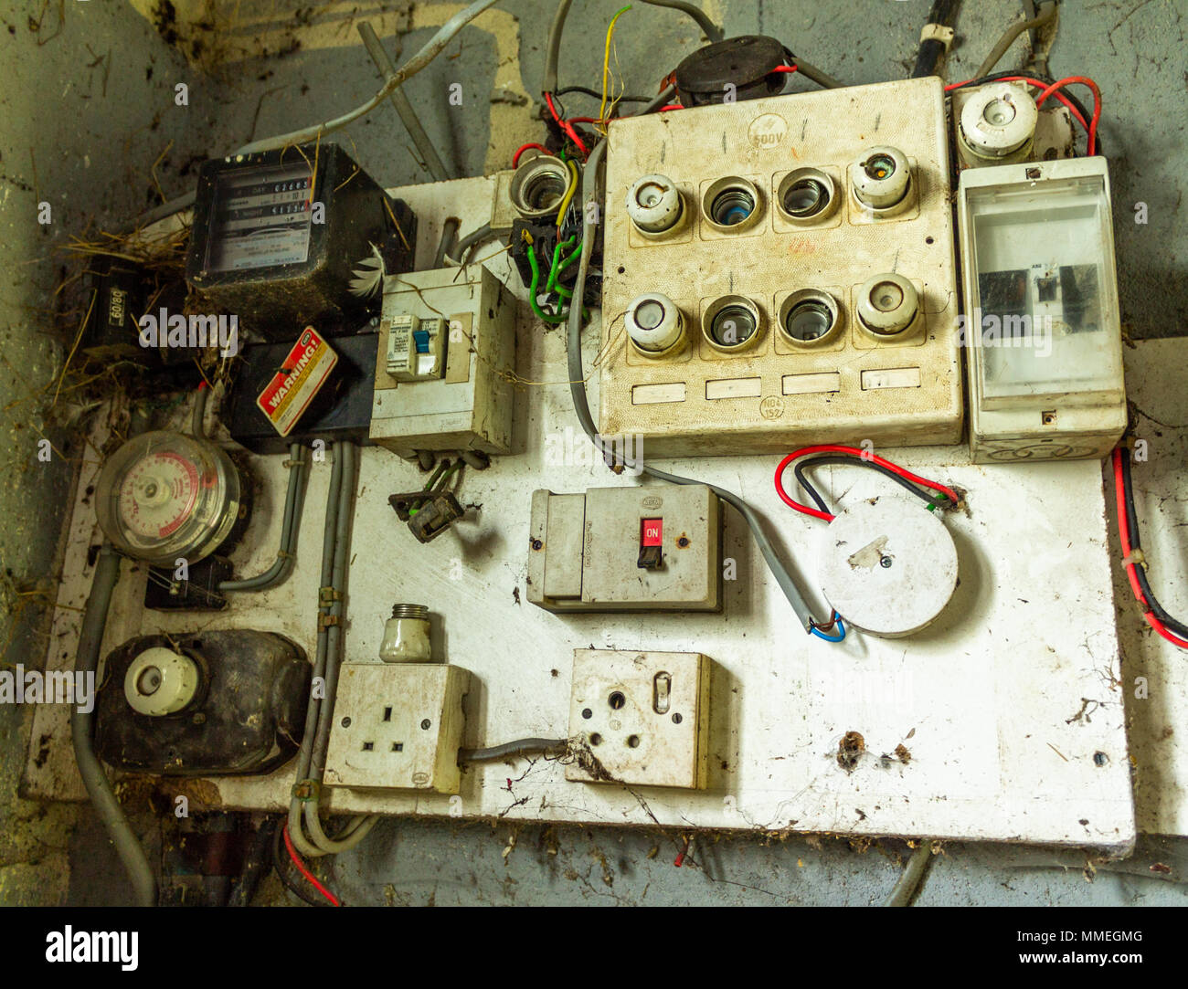 old electrical distribution board with electric meter fuse box fuse board and electric switches with the wiring attached MMEGMG electrical distribution board stock photos & electrical distribution