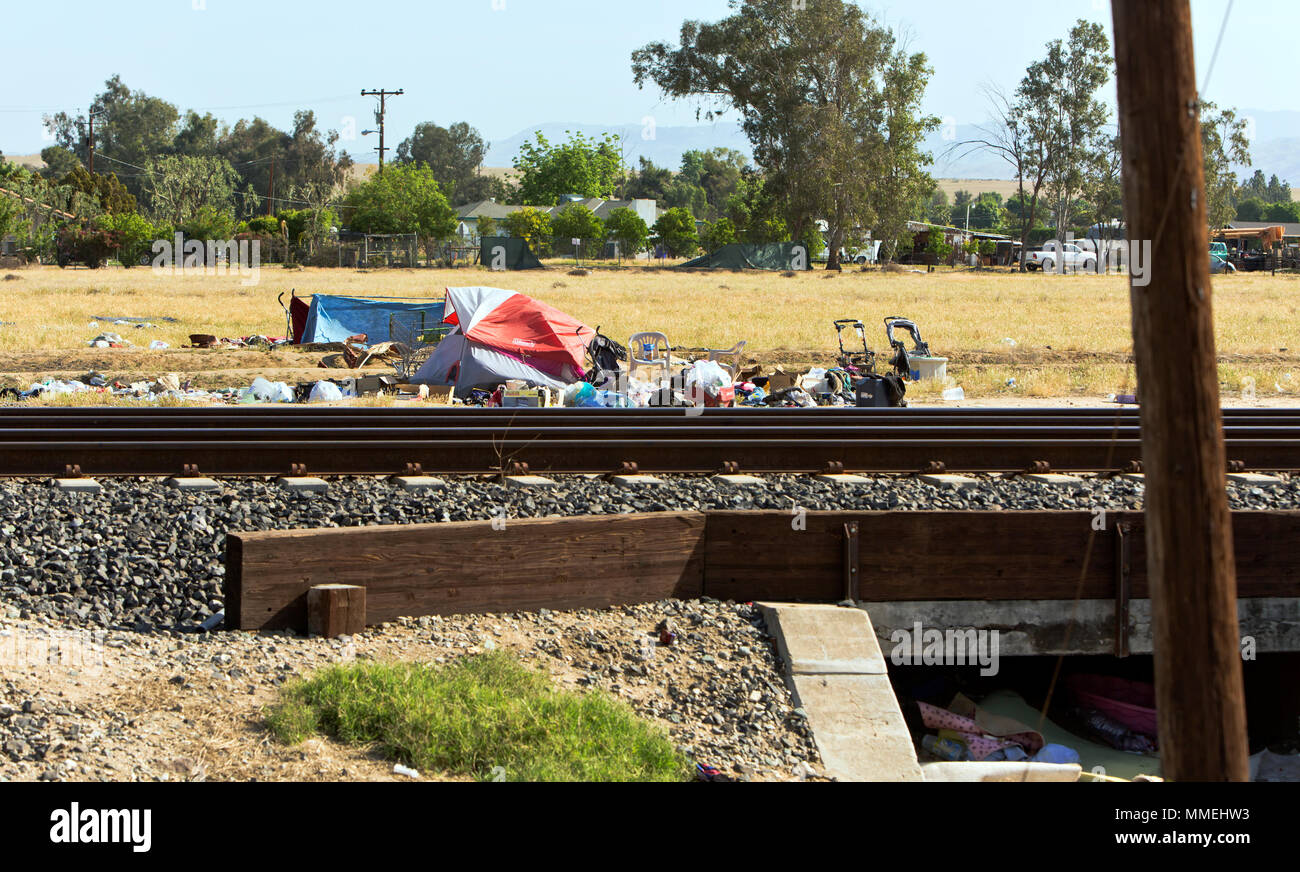 Homeless Camp, railroad tracks, rural Kern County road, scattered trash, fenced subdivision in background. - Stock Image