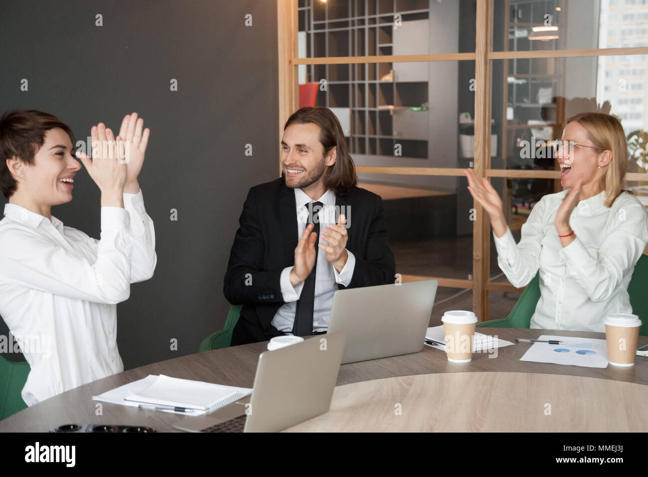 Excited business team applauding congratulating partner with suc Stock Photo