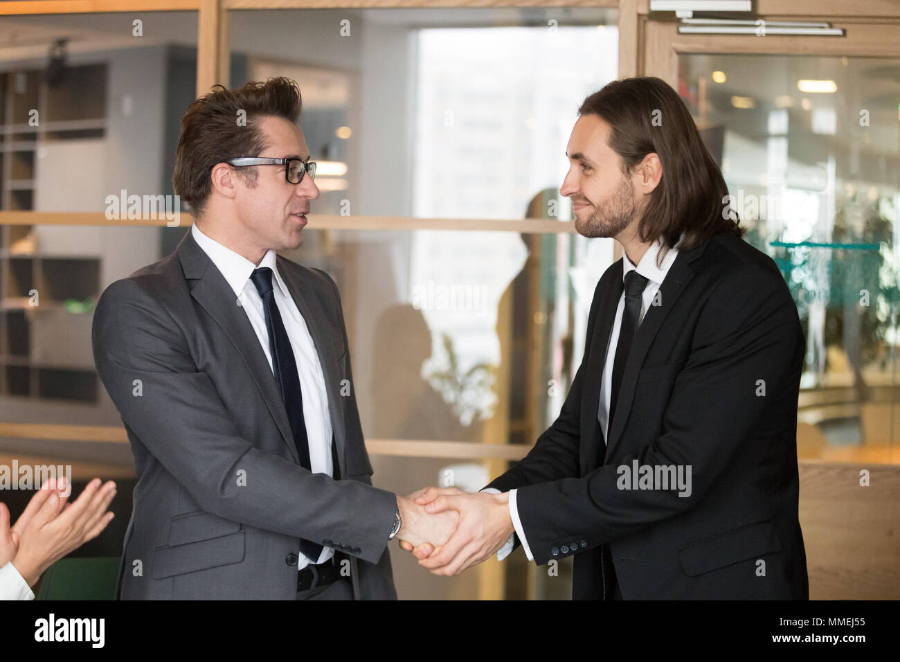 Smiling businessmen shaking hands, making deal, gratitude or pro - Stock Image