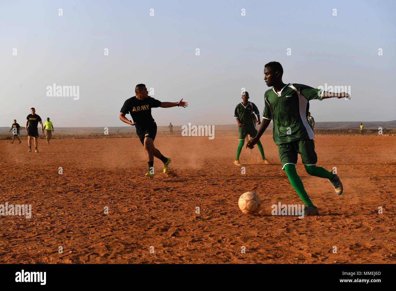 U.S. Army infantry soldiers from 10th Mountain Division and 3-144 Infantry Regiment and members of the Djibouti Armed Forces (FAD) assigned to the Rapid Intervention Battalion, play soccer in Djibouti May 10, 2018, May 10, 2018. Members of the RIB go through a five week course covering combatives, weapons, and combat lifesaving skills. (U.S. Air Force photo by Airman 1st Class Haley D. Phillips). () Stock Photo