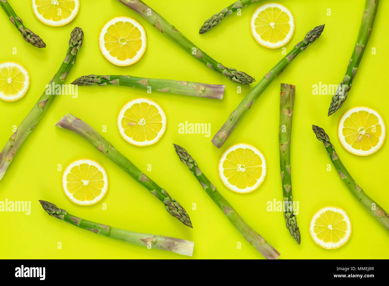 Beautiful food art background. Asparagus sprouts and sliced lemon on bright green surface. - Stock Image