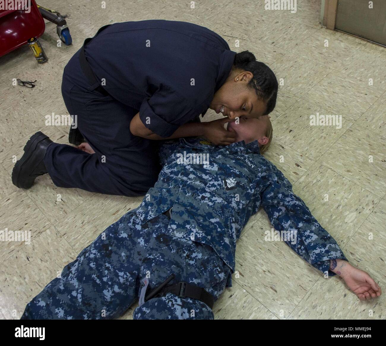 180511-N-NH199-0154 PACIFIC OCEAN (May 11, 2018) Hospital Corpsman 1st Class Stacie Coursey (left), from Fairfield, Calif. assesses a mock patient's airway during a tactical combat casualty care (TCCC) course aboard Military Sealift Command hospital ship USNS Mercy (T-AH 19), May 10, 2018. Mercy is currently deployed in support of Pacific Partnership 2018 (PP18). PP18's mission is to work collectively with host and partner nations to enhance regional interoperability and disaster response capabilities, increase stability and security in the region, and foster new and enduring friendships acros - Stock Image