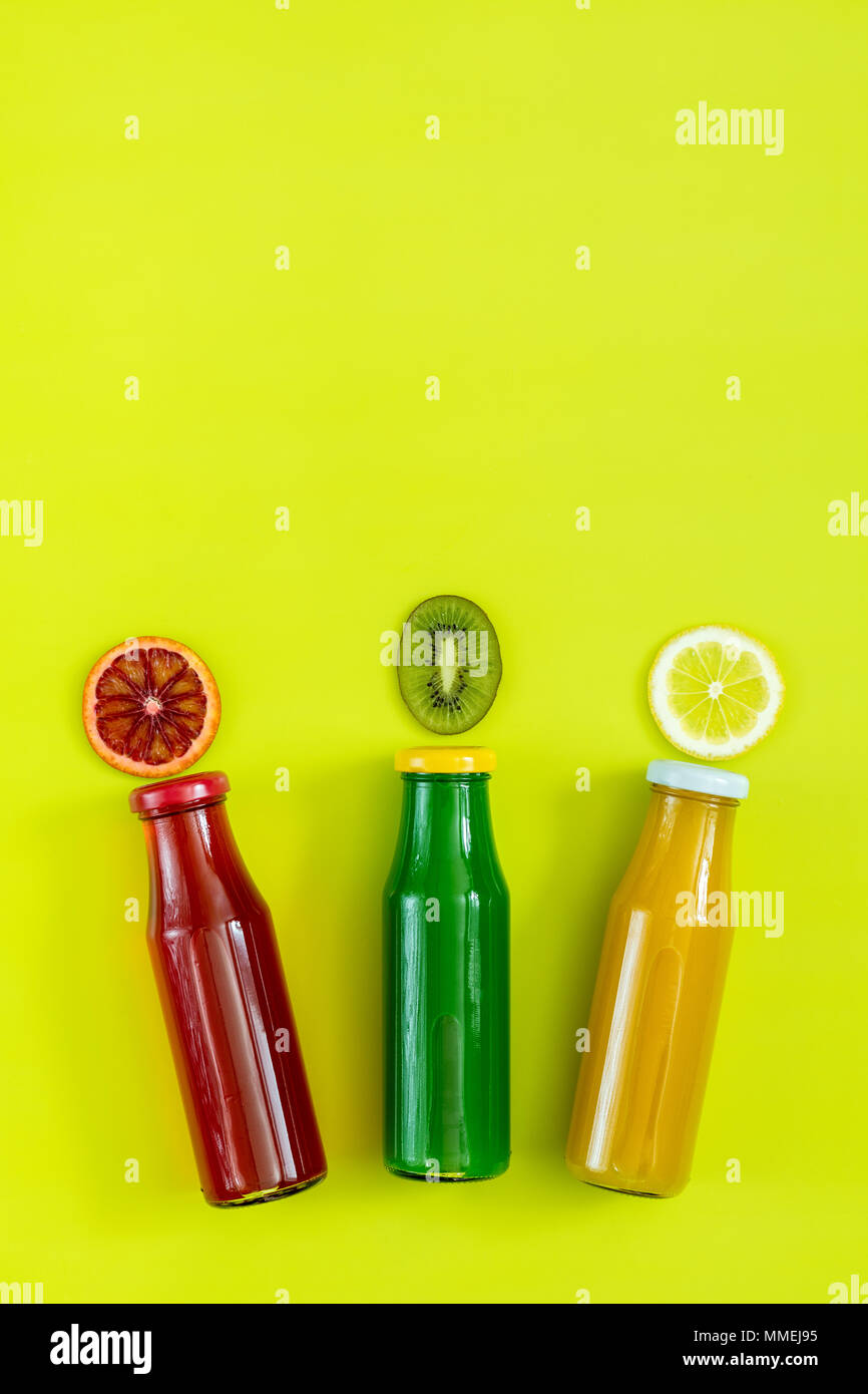 Beautiful food art background. Yellow, red and green juices in glass bottles sliced lemon, kiwi and blood orange fruit on bright green surface. - Stock Image