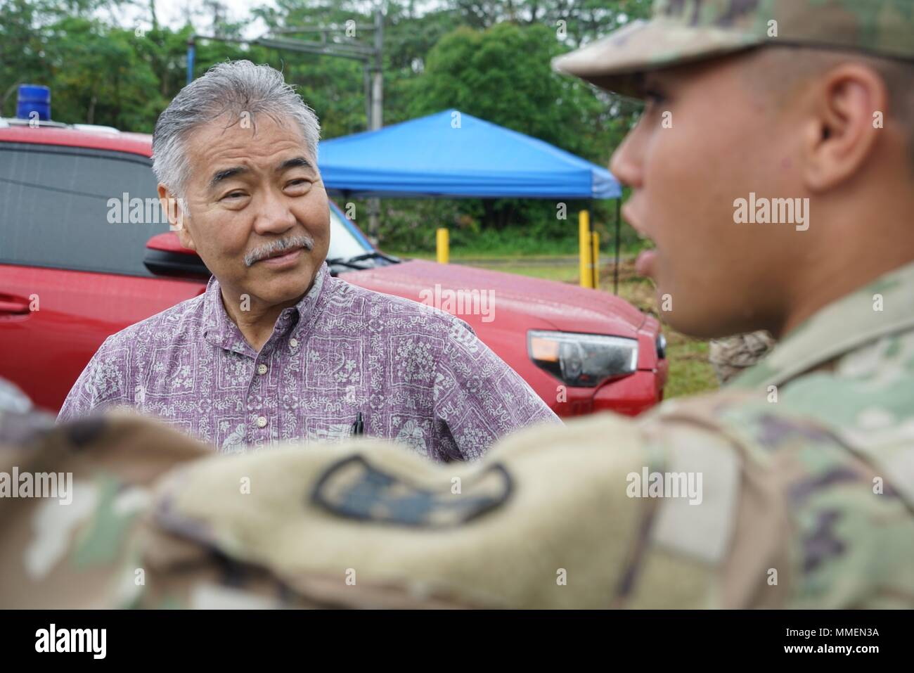 Hawaii Governor David Ige is briefed by National Guardsmen PFC Hoaka Corteskanaina, right, during a visit to the area affected by the Kilauea volcano eruption May 8, 2018 in Pahoa, Hawaii. The recent eruption continues destroying homes, forcing evacuations and spewing lava and poison gas on the Big Island of Hawaii. - Stock Image