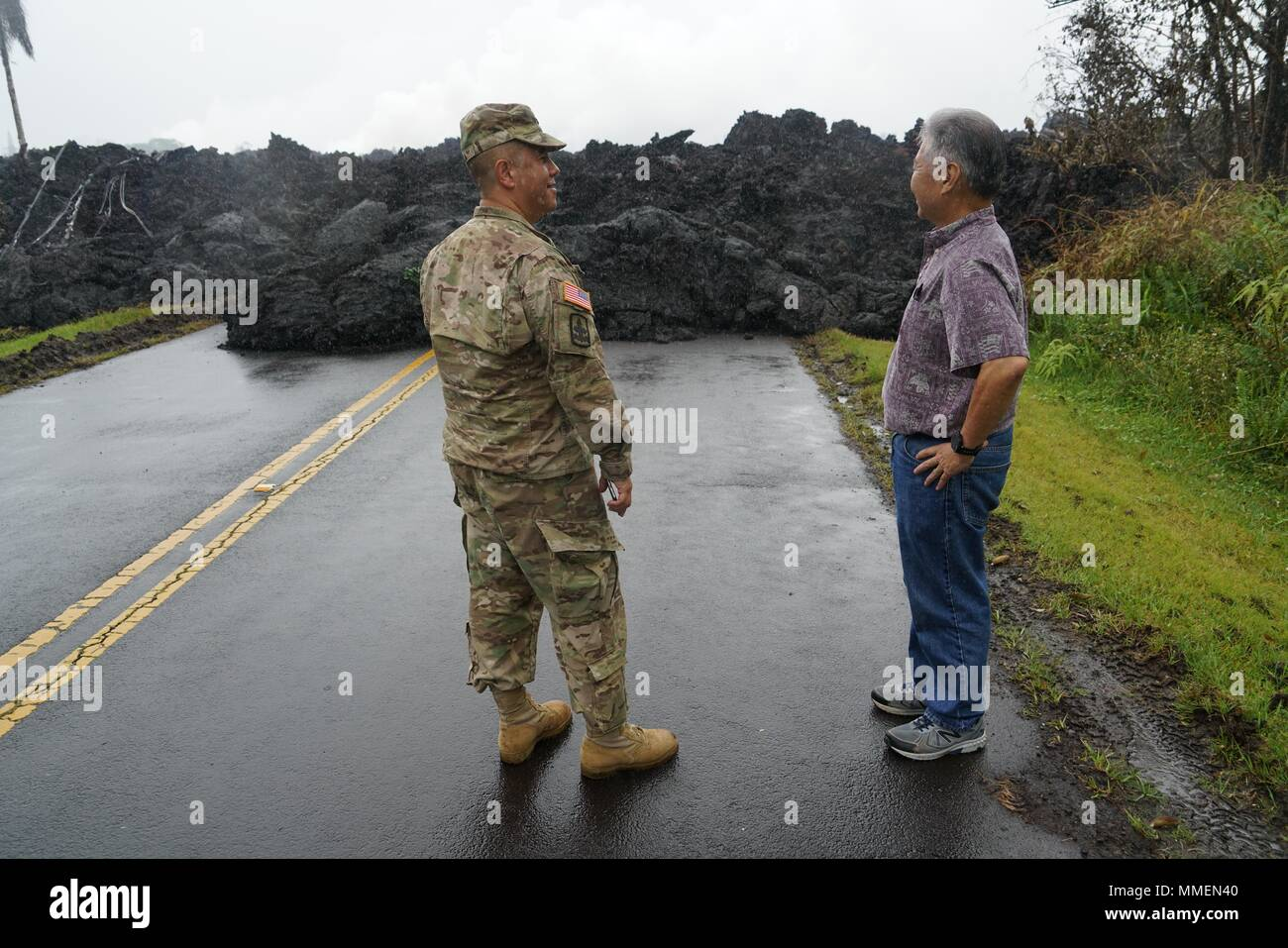 Hawaii Governor David Ige is briefed by National Guard Brig. Gen. Kenneth Hara, left, during a visit to the area affected by the Kilauea volcano eruption May 8, 2018 in Pahoa, Hawaii. The recent eruption continues destroying homes, forcing evacuations and spewing lava and poison gas on the Big Island of Hawaii. - Stock Image