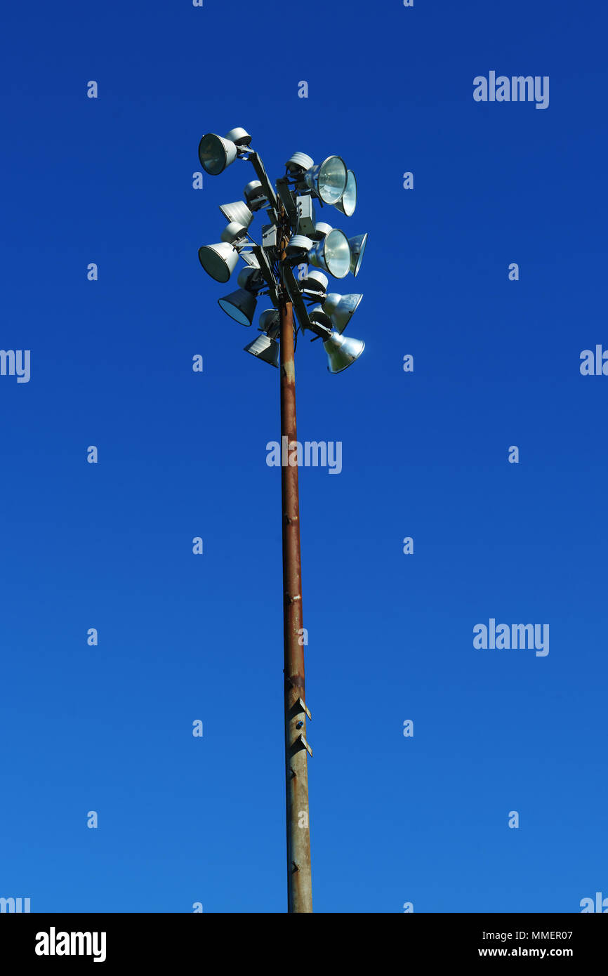 Rusty sport light post in a stadium against a deep blue sky Stock