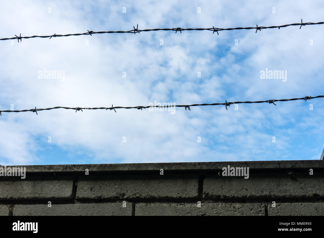 Barbed wire fence against the blue sky with clouds - Stock Image
