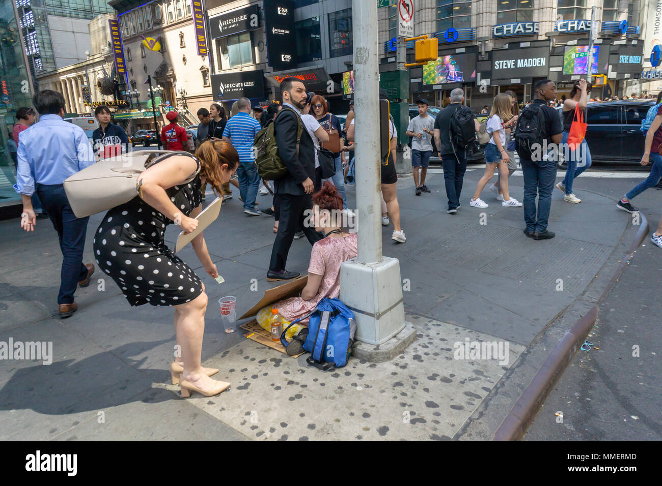 A woman gives money to a homeless woman begging in Midtown Manhattan in New York on Thursday, May 3, 2018. (© Richard B. Levine) - Stock Image