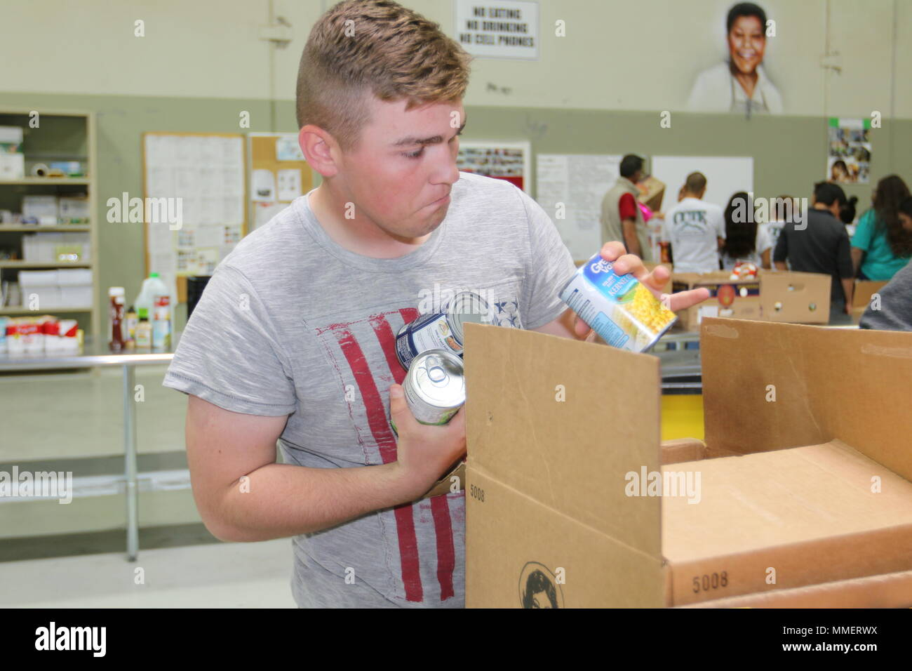 Pvt. Mason Landeros, combat medic specialist, 3rd Armored Brigade Combat Team, helps to sorts and packs food at El Pasoans Fighting Hunger Food Bank in El Paso, Texas, Oct. 28, 2017. Feels giving back to the community is better than sitting at home and playing video games. (U.S. Army Photo by Staff Sgt. Felicia Jagdatt) - Stock Image