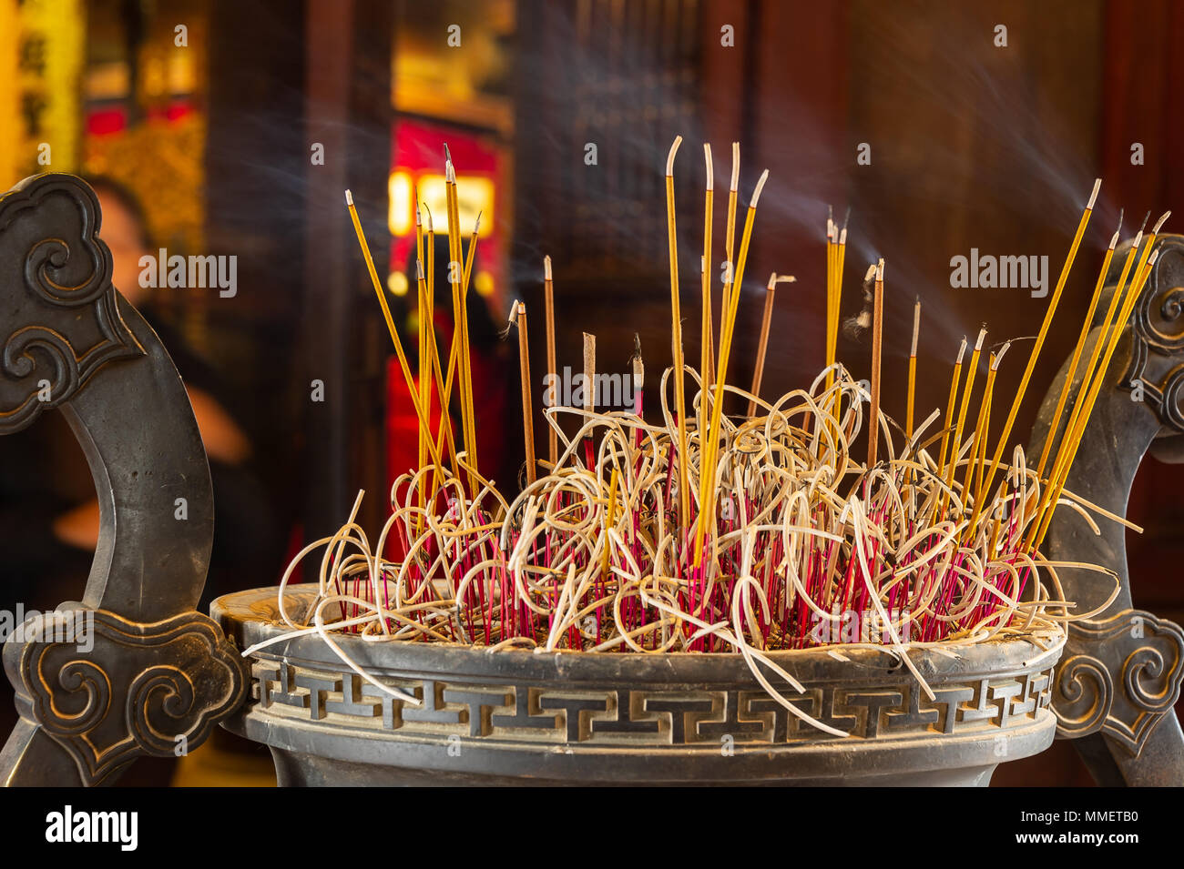An urn with brightly colored burning incense at the entrance to a temple in Viet Nam - Stock Image