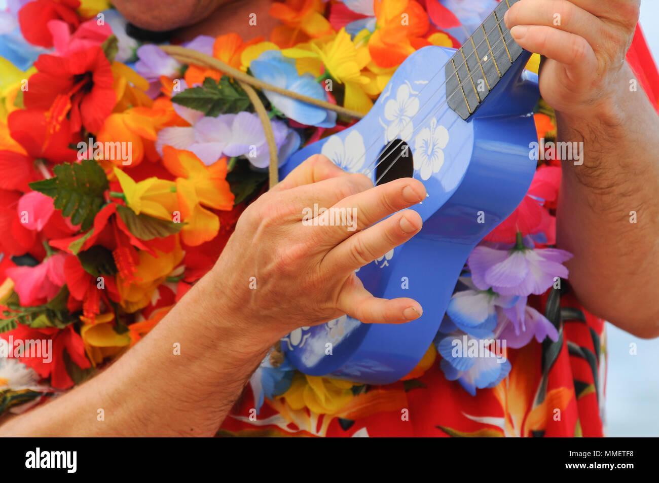 Man in bright floral Hawaiian shirt strumming a blue ukulele - Stock Image