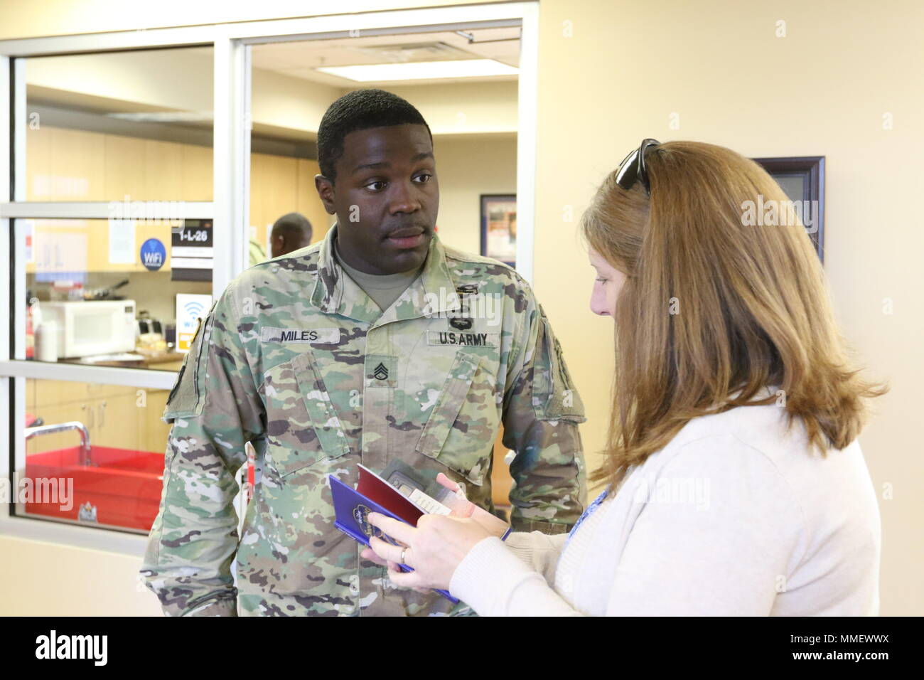 """Staff Sgt. Contavious L. Miles, Chicago native, civil affairs specialist, 97th Civil Affairs Battalion (Airborne), 95th CA Brigade (A), shows Beverly Jackson, USO of North Carolina, one copy of the Disney classic """"Snow White and the Seven Dwarfs,"""" Oct. 26, Fort Bragg, N.C. This was one of 250 books Miles donated to the USO to be distributed during USO events. (photo by Sgt. 1st Class Thomas Collins, released) Stock Photo"""