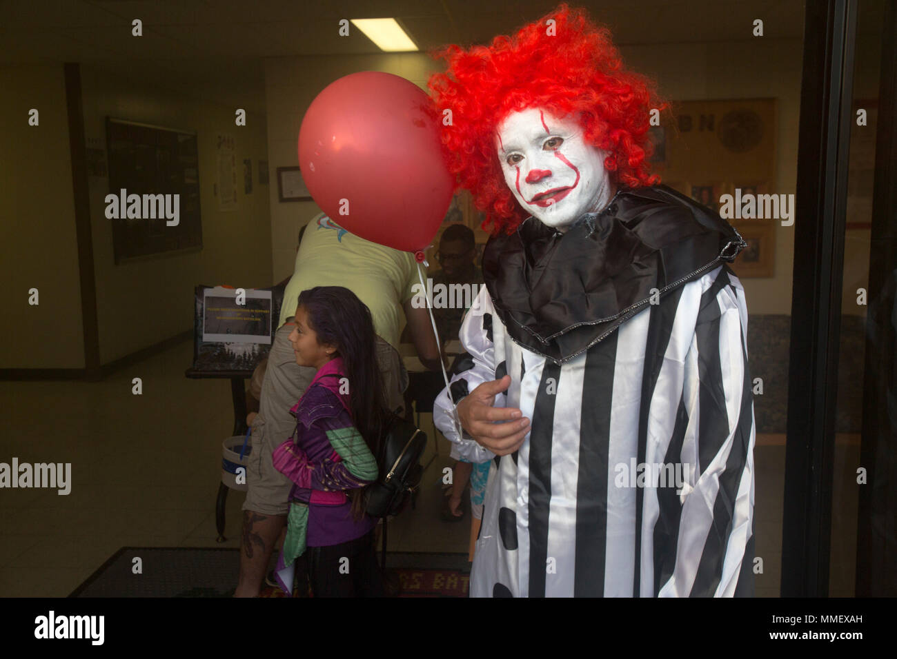 """Sgt. Maj. Phillip Billiot, sergeant major of Headquarters Battalion (HQBN), dresses up as Stephen King's """"Pennywise"""" character during the Trunk-or-Treat Halloween event, Marine Corps Base Hawaii (MCBH), Oct. 27, 2017. The event invited Marines, Sailors, and their families to dress up, decorate their vehicles, and attend the haunted house organized by the battalion's family readiness officer and senior leadership. Social events hosted aboard MCBH accommodate a positive community which fosters, develops and promotes resiliency within the installation. (U.S. Marine Corps photo by Lance Cpl. Luke  - Stock Image"""