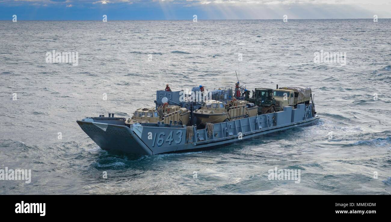ATLANTIC OCEAN (Oct. 30, 2017) Landing craft utility 1643, attached to Assault Craft Unit (ACU) 2, departs the amphibious assault ship USS Iwo Jima (LHD 7). Iwo Jima is underway conducting routine operations at sea. (U.S. Navy photo by Mass Communication Specialist 3rd Class Kevin Leitner/Released) - Stock Image