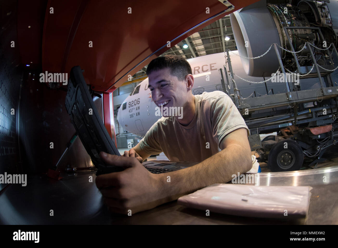 U.S. Air Force Senior Airman Taylor Corliss, 721st Aircraft Maintenance Squadron aerospace propulsion journeyman, reads schematics to a C-17 Globemaster III engine at a hangar on Ramstein Air Base, Germany, Oct. 27, 2017. The 721st AMXS works on aircraft from all over Air Mobility Command. (U.S. Air Force photo by Senior Airman Devin Boyer) - Stock Image