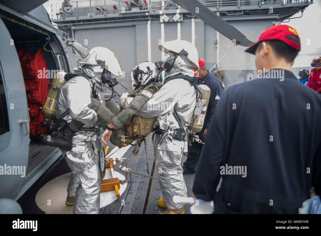 """171030-N-DO281-133  ATLANTIC OCEAN (Oct. 30, 2017) Damage Controlman 1st Class Robert Gamble and Damage Controlman 2nd Class Steven Maldonado remove Naval Aircrewman (Tactical Helicopter) 3rd Class Stephen Loftin,  assigned to the """"Vipers"""" of Helicopter Maritime Strike Squadron (HSM) 48, from a MH-60R Sea Hawk helicopter  aboard the guided-missile cruiser USS Monterey (CG 61). Monterey is deployed in support of maritime security operations in the U.S. 5th and 6th fleet area of operations. (U.S. Navy photo by Mass Communication Specialist Seaman Trey Fowler/Released) Stock Photo"""