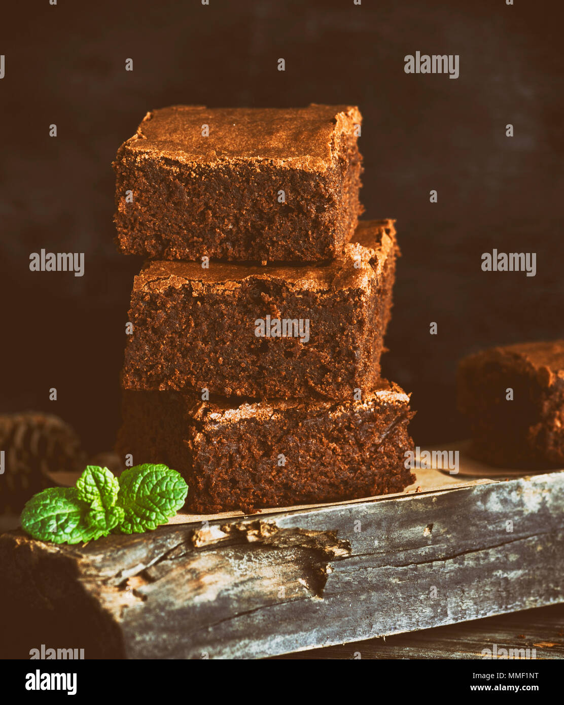 square pieces of chocolate baked brownie pie on a  wooden board, vintage toning - Stock Image