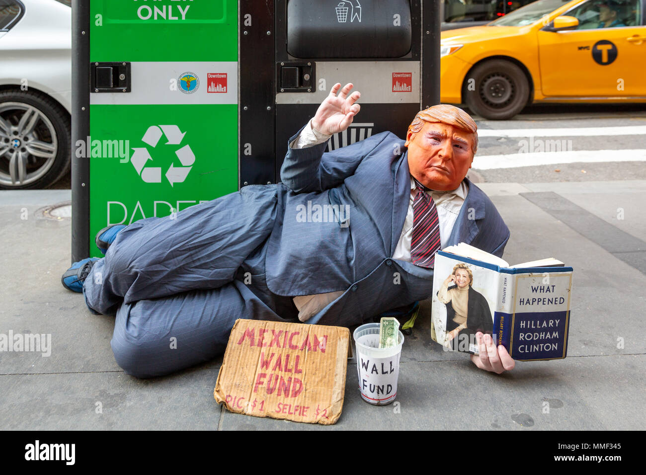 NEW YORK -  MAY 3, 2018: Funny street beggar wears a Trump mask and a dirty businessman suit. The man mocks the current American president and asks to - Stock Image
