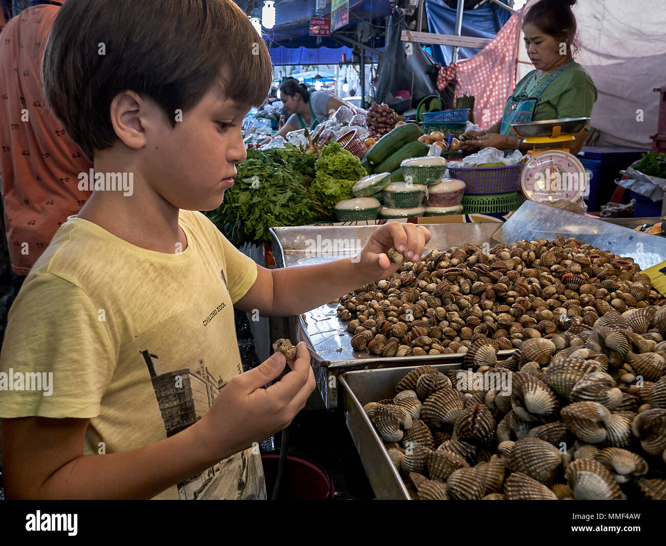 Curiosity. Young boy curiously studying snails at a Thailand street market stall. - Stock Image