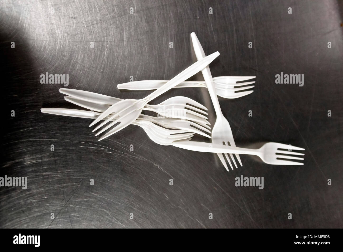 Artistic Arrangement of plastic forks on a scratched stainless steel surface still life - Stock Image