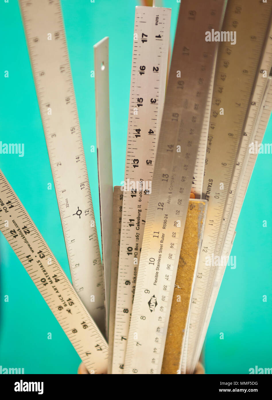 Still life of a collection of rulers on a plain blue background - Stock Image