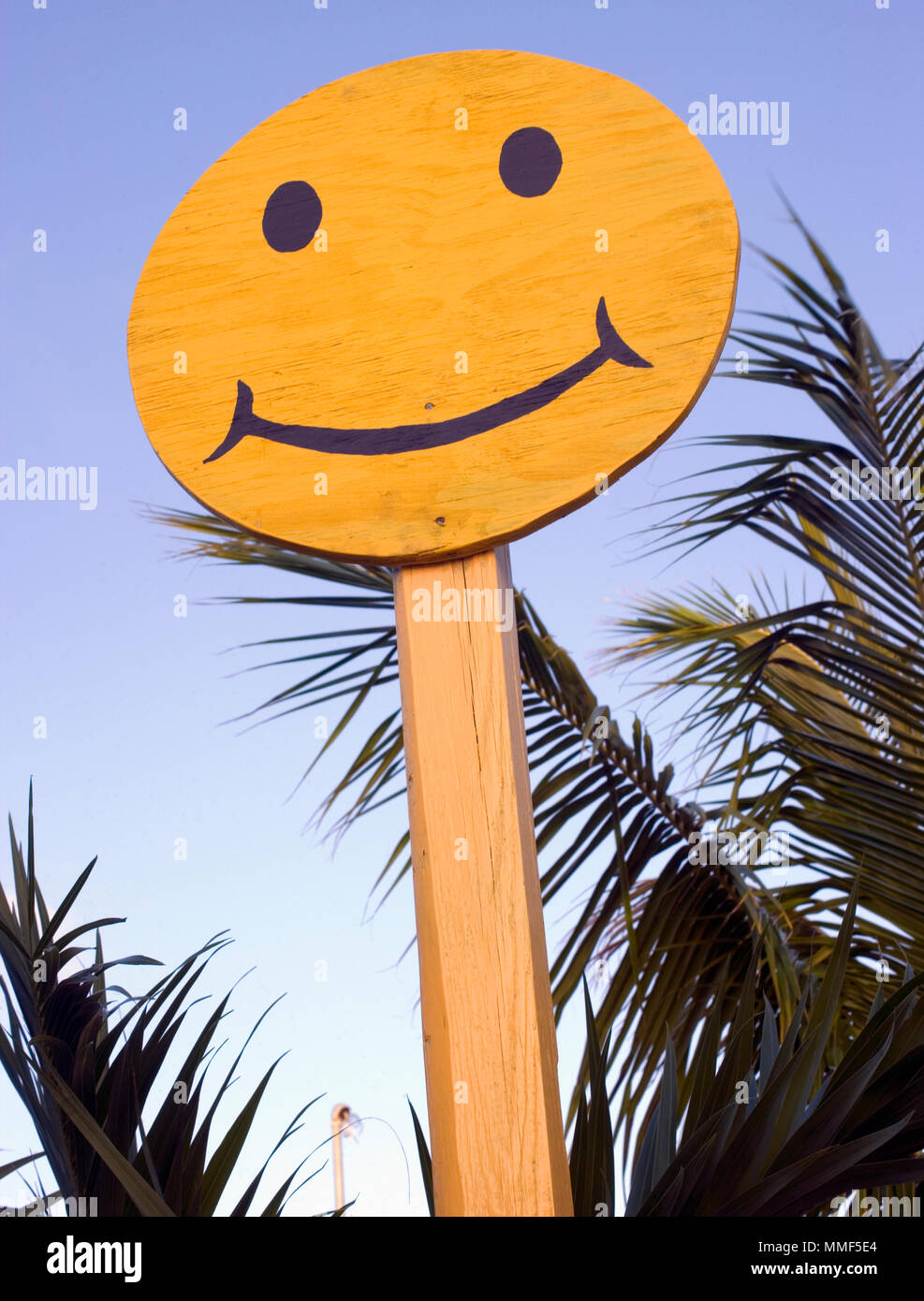 Plywood happy face sign with palm trees in the Bahamas Stock Photo