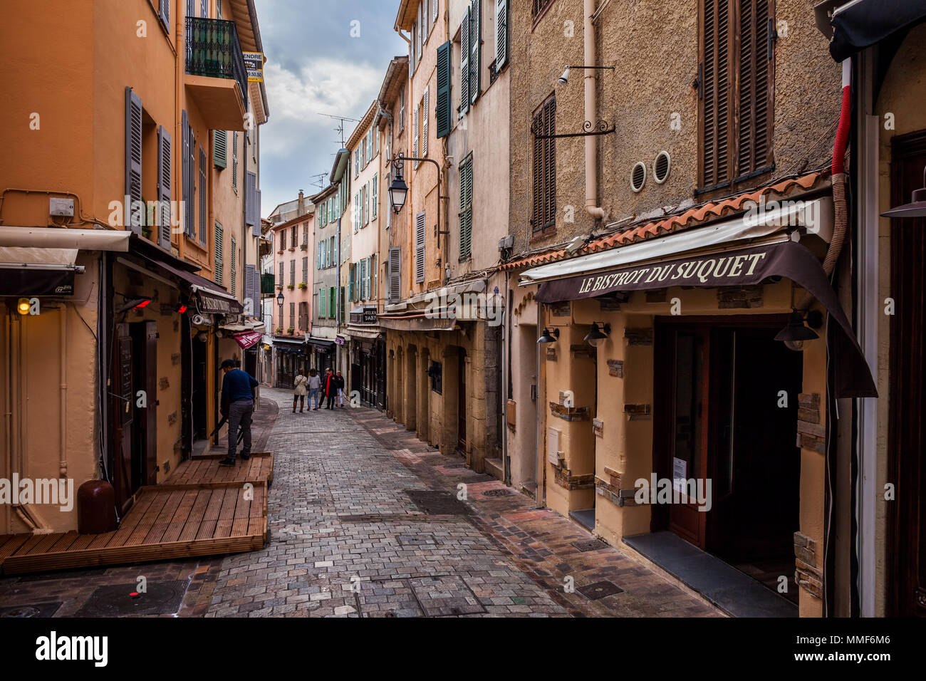 Narrow street in Le Suquet, Old Town of Cannes city in France, on the right Le Bistrot du Suquet restaurant - Stock Image