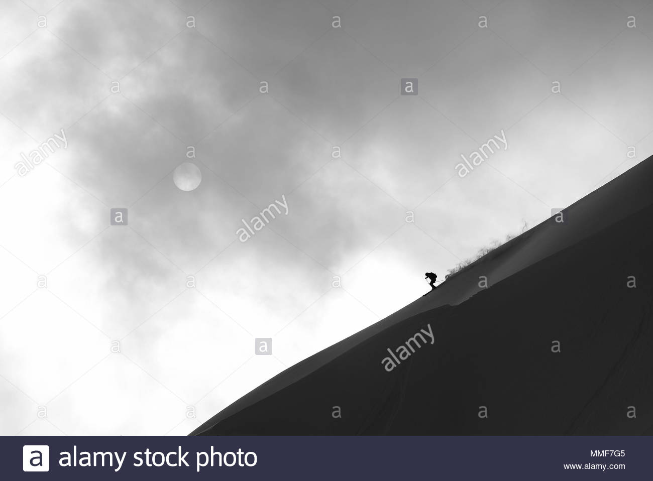 A skier runs down the skyline with the sun behind clouds. - Stock Image
