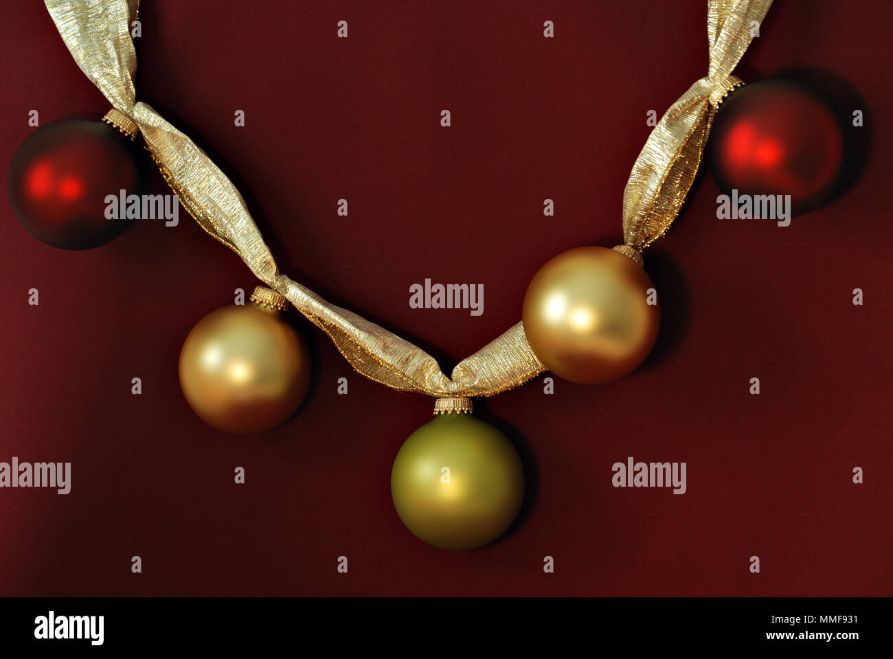 red gold and green christmas ornaments on a dark red background