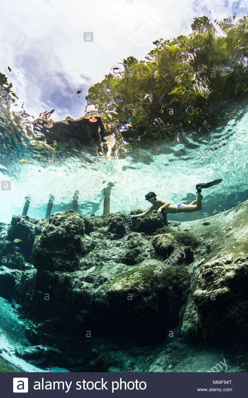 A snorkeler hovers near the limestone canyons at Blue Spring, cloudy blue skies overhead. - Stock Image