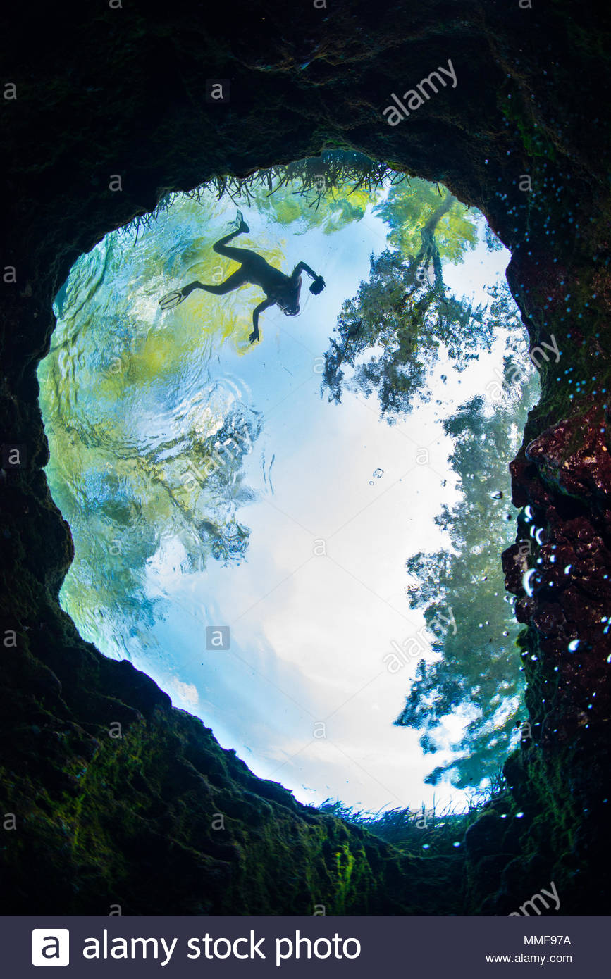 The oval spring vent at Jug Hole and a silhouetted swimmer. - Stock Image